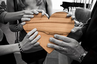 Hands holding wooden heart